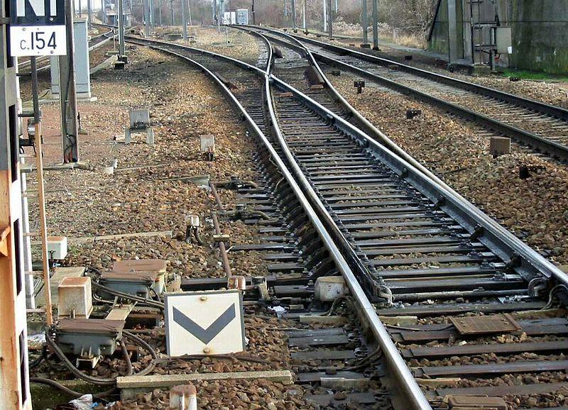 Aiguillage simple en gare d'Épône - Le chevron pointe bas noir sur fond blanc : Dans la signalisation SNCF, cette pancarte indique que le train aborde un aiguillage ou une série d'aiguilles par la pointe. Elle marque le début d'une limitation de vitesse.