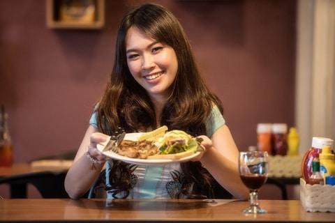 femme au large sourire qui tend une assiette pleine