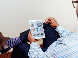 homme utilisant une tablette tactile pour ses bilans