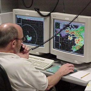 météorologue assis derrière un bureau